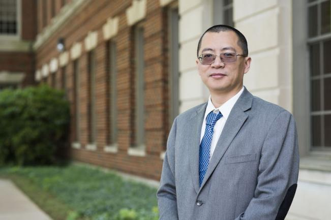 Xiong Jiang stands in front of the Medical-Dental Building at Georgetown