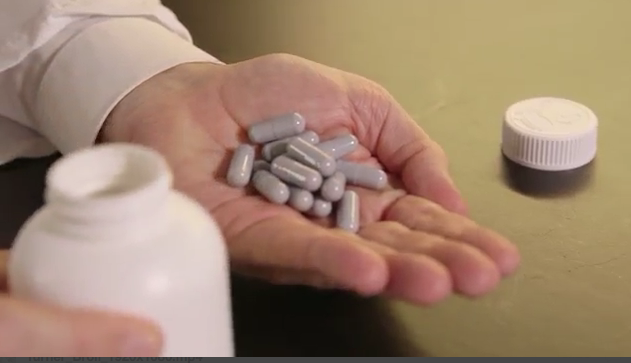 A hand holds a mound of pills