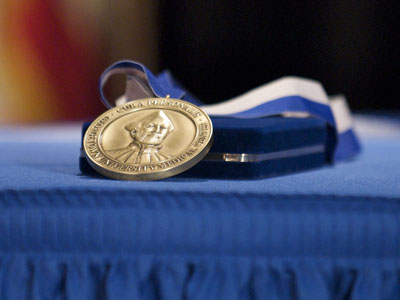 The Cura Personalis medal rests on a blue tableclothed table