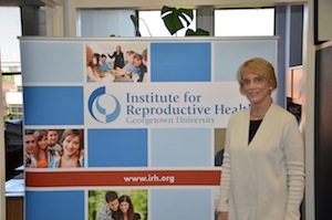 Victoria Jennings stands in front of a sign for the Institute for Reproductive Health
