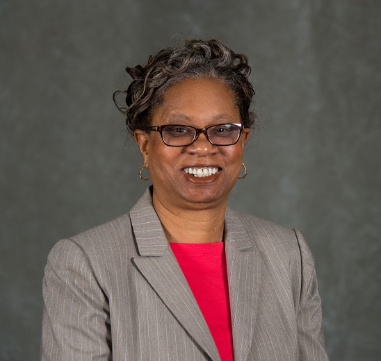A portrait of Ms. Adams-Cambell in which she is wearing glasses and a gray suit with red shirt