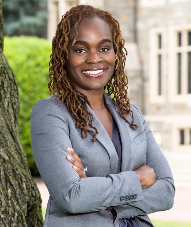 Ms. Breland-Noble is pictured wearing a gray suit and standing with her arms crossed with a tree, greenery, and building in the background.