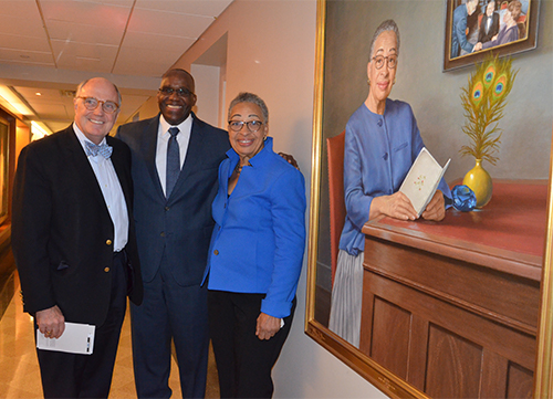 Stephen Ray Mitchell, David Taylor, and Joy Phinizy Williams stand side by side in a hallway next to the portrait of Williams
