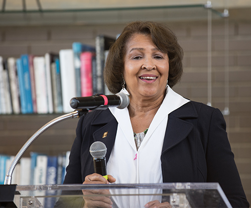 Doris Brown speaks at a podium with shelves of books in the background behind her