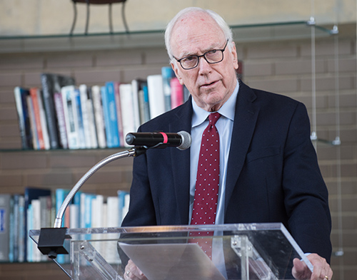 Dr. Edward Healton speaking at a podium, with shelves of books behind him