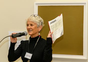 Caroline Wellbery holds up a copy of her journal article as she speaks into a microphone at a podium