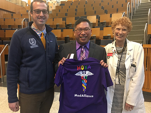 Three individuals stand next to each other in an auditorium setting, the center individual holds a purple Hoya MedAlliance shirt