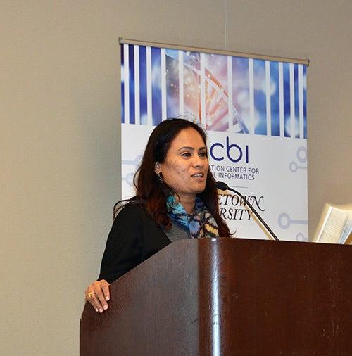 Subha Madhavan stands at a podium