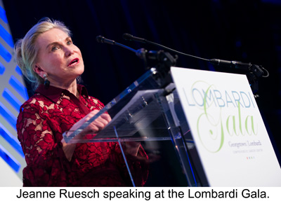 """Jeanne Ruesch speaks at a podium behind a sign that reads """"Lombardi Gala."""""""