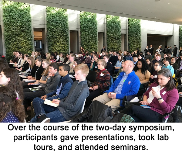 Student participants sit in rows in the audience at the symposium
