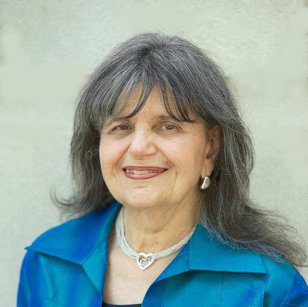 In this portrait image, Ms. Magrab wears blue and is pictured against a beige backdrop.