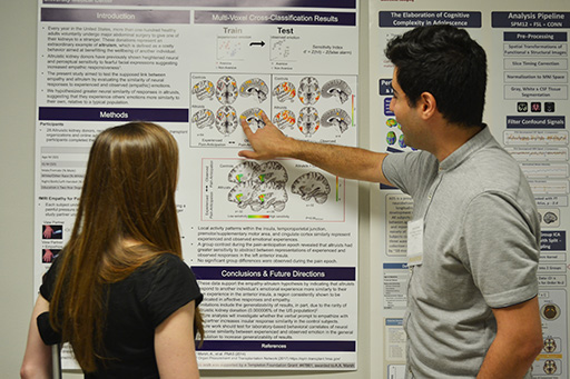 two students standing in front of a research poster with graphics of brains on it, facing the poster, with the student on the right pointing at the poster