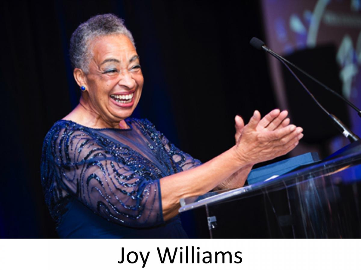 Joy Williams stands at a podium, smiling and clapping