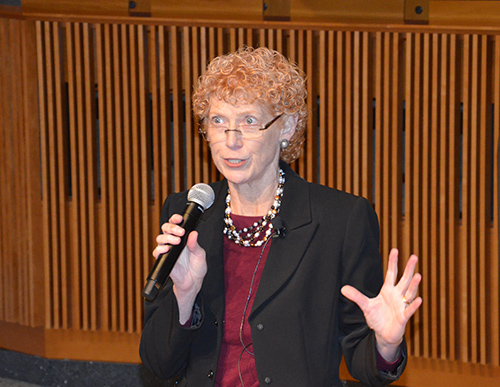 Eileen Moore stands with a microphone in an auditorium
