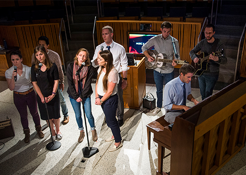A group of medical students sings and plays musical instruments before an audience