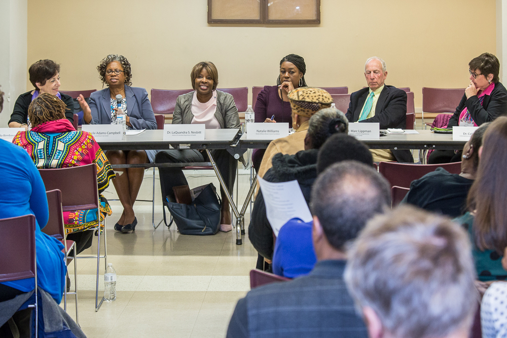 A group of panelists sits at a table before a group of community members from Washington, D.C.'s Wards 7 & 8