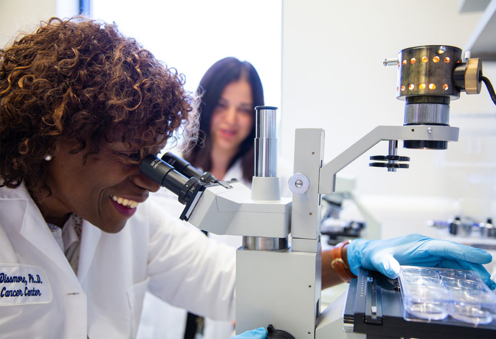 A female researcher looks through a microscope at a sample she holds in her hand, while another researcher looks on