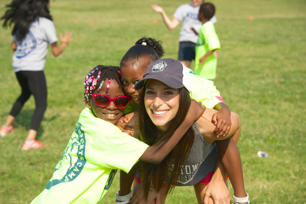 A female medical student gets hugs from two girls participating in the summer camp run by SOM students