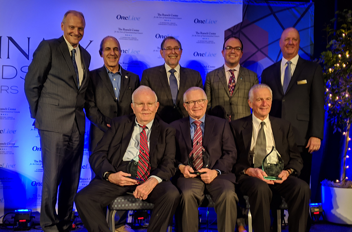 A group of men smiles onstage; three men in the front row hold crystal awards.