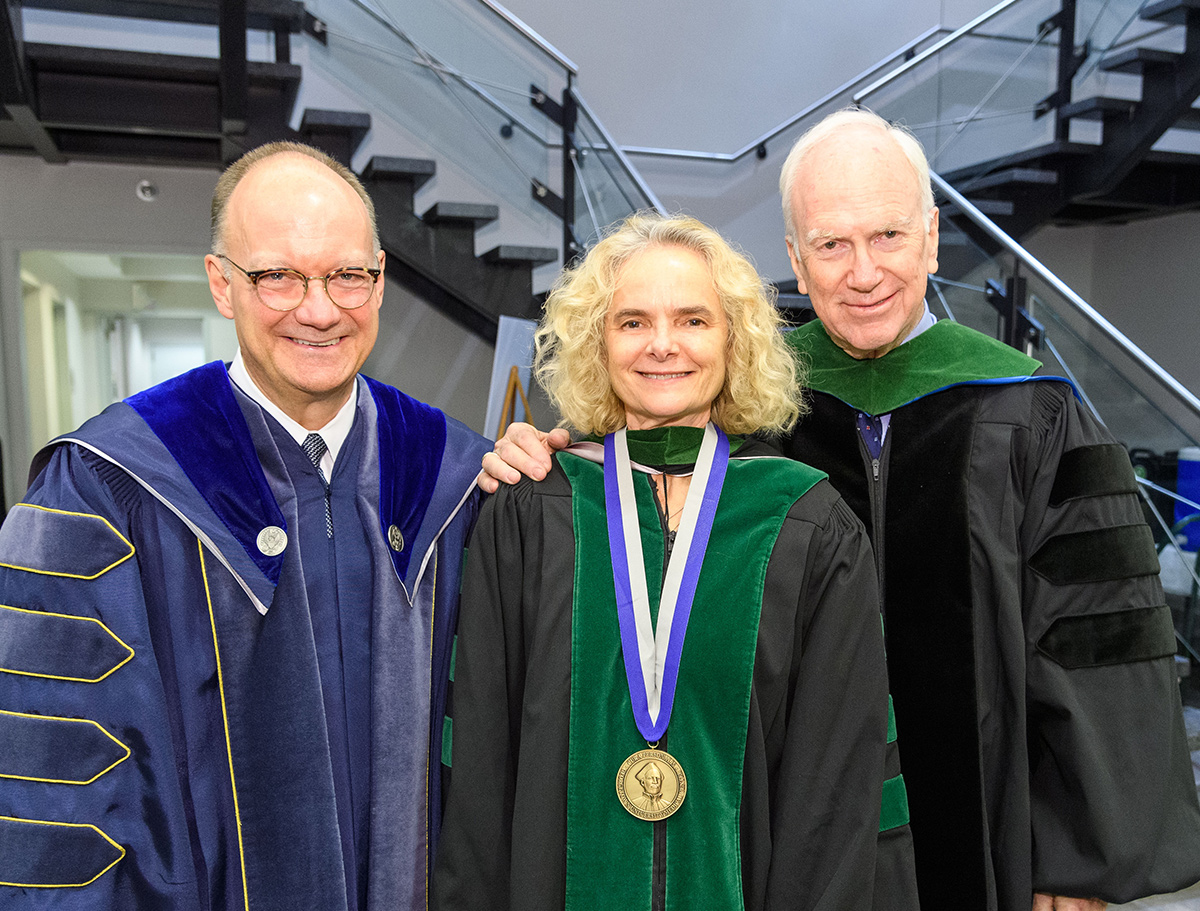 Jack DeGioia, Nora Volkow, and Dr. Ed Healton stand side by side in academic regalia