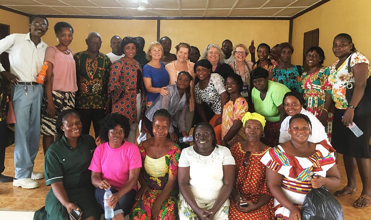 A large group of workshop participants stands together for a group photo in Liberia