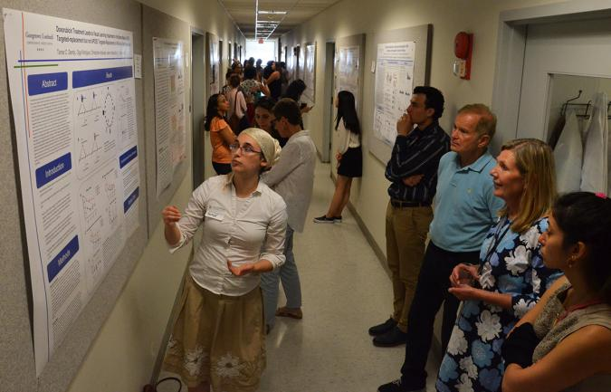 A student presents her poster for onlookers