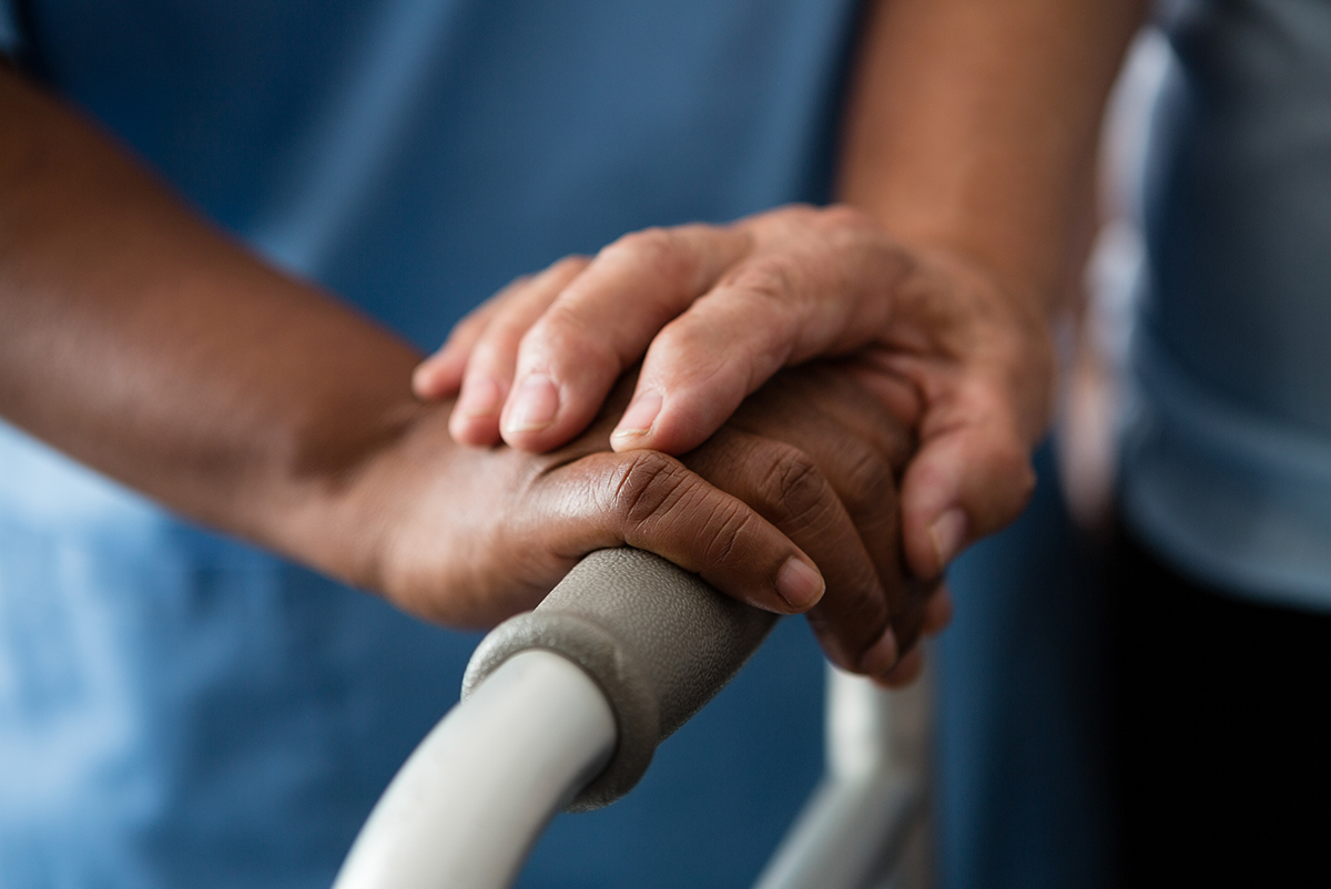 Image of hands and a walker symbolizing support of the aging