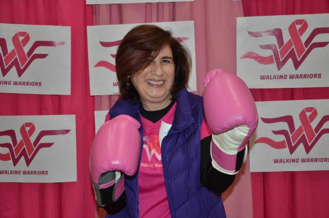 A woman poses in pink boxing gloves.