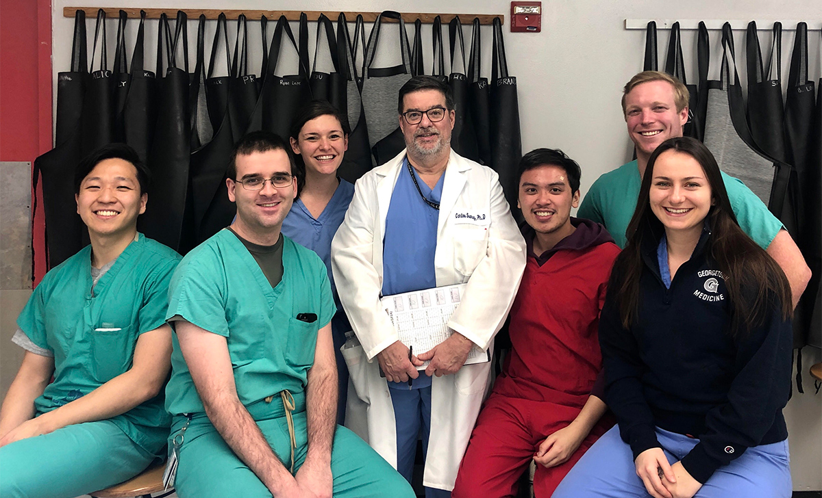 A group of medical students sits with their professor in a group image. Behind them are rows of aprons used in the lab.