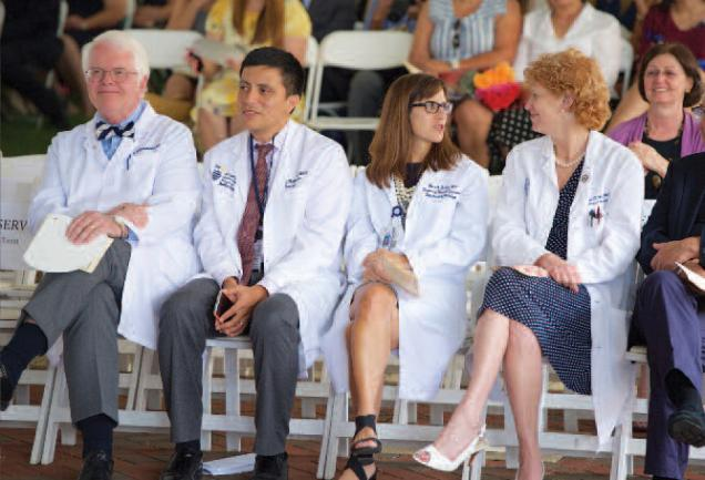 A group of doctors sit side by side at an event