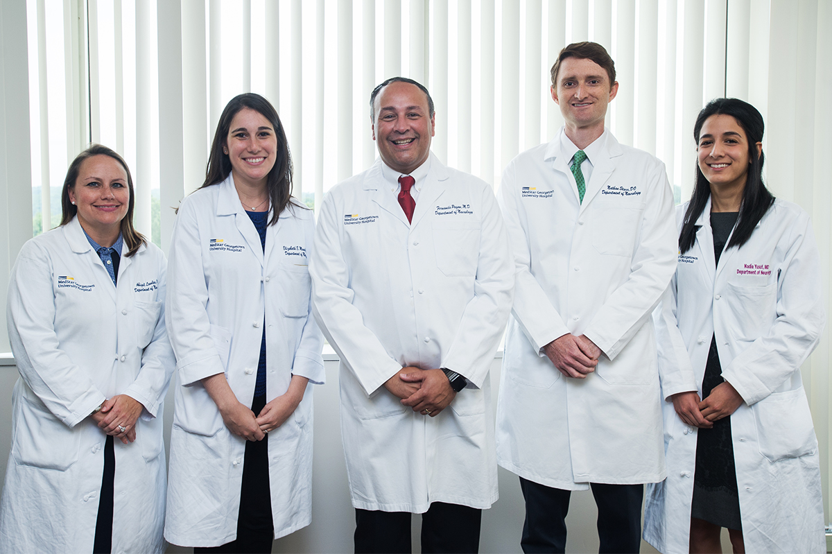 Fernando Pagan, MD, stands with several male and female participants in the Movement Disorders Fellowship Program