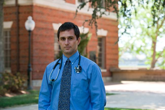 Dr. Merenstein stands outdoors near a red brick building