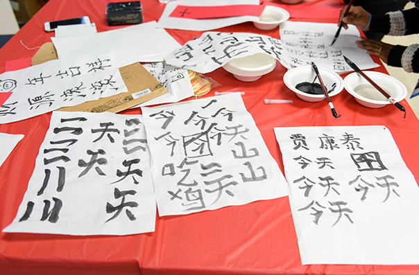 A red tablecloth on which is set white paper with Chinese calligraphy in black ink.