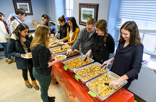 Students file past a table laden with pans of food that other students stand ready to serve them from.