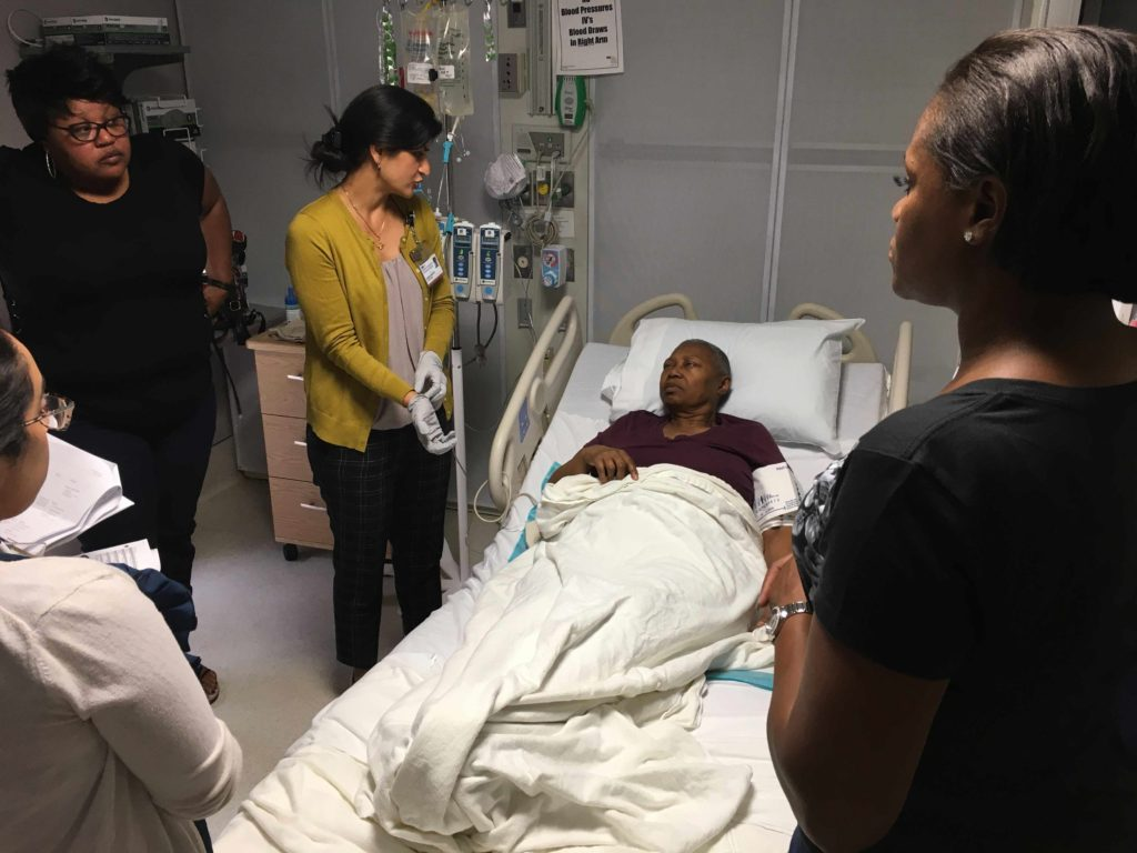 A patient rests in bed while family members and a caregiver stand by her side.