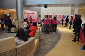 A group of people dressed in pink listen to a woman giving remarks.