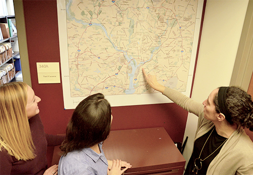 Three women stand and look at a map of the D.C. area; one of the women points at something on the map