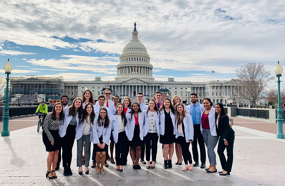 A group of medical students stands outdoors before the U.S. Capitol Building