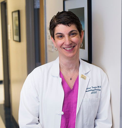 Claudine Isaacs, MD, stands in a hallway