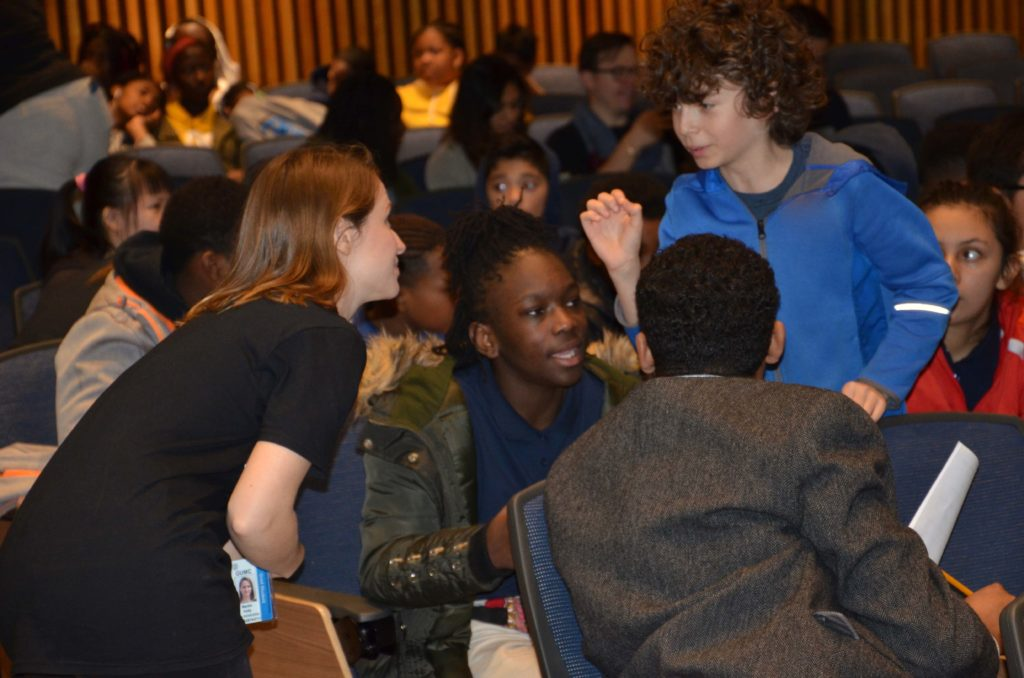 A female graduate student listens carefully to a male middle school student.