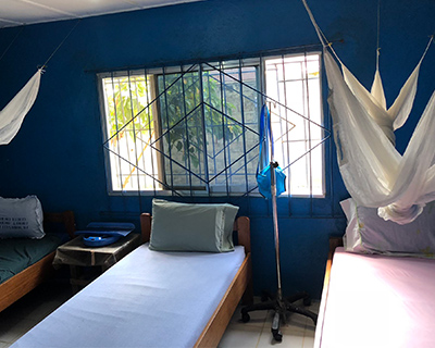 Beds made with pastel-colored sheets are neatly arranged in a room with blue walls and a window. Bed nets hang from the ceiling.