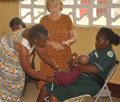 A woman sits with equipment simulating a postpartum woman on her lap, while another woman does a mock exam, guided by a third woman