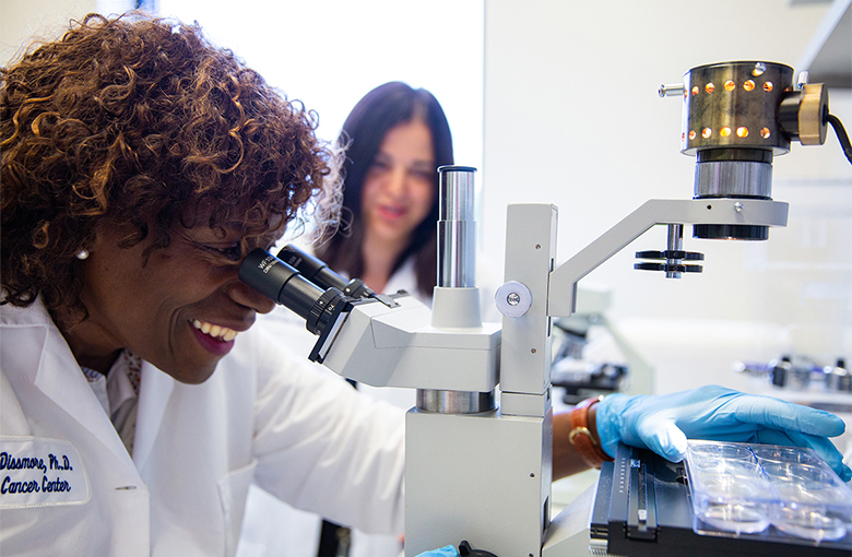 A female researcher in lab coat looks through a microscope while another researcher out of focus in the background looks on.