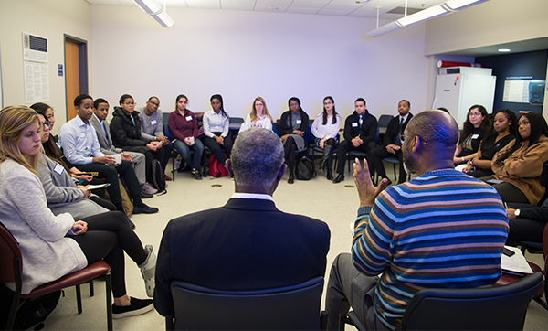 A room ringed with students in chairs looking at two African American men speaking.