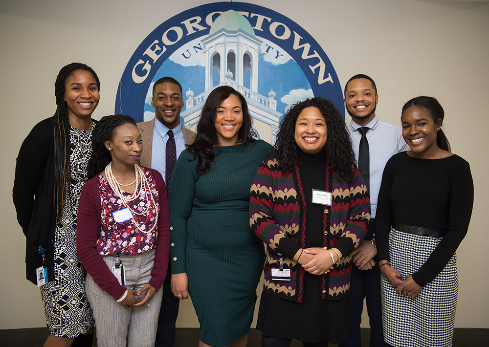 A group of students of color stand together in front of a wall with a mural that says Georgetown