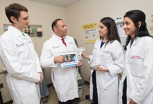 Dr. Pagan stands with three fellows in his program, two female and one male