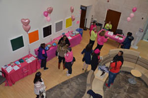A pink-themed room with balloons and people mingling.