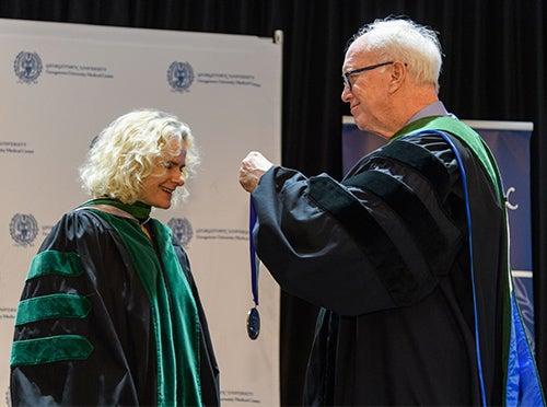 Nora Volkow, MD, accepts the Cura Personalis award from Edward Healton