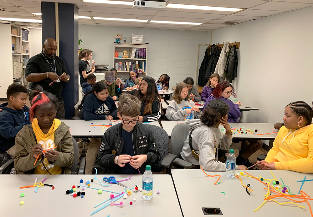 Students sit at tables working with pom-pom balls and chenille stems