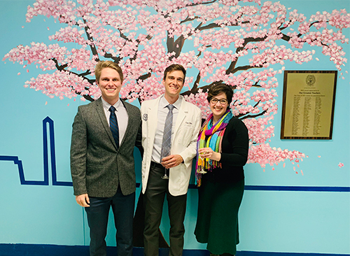 Three individuals stand side by side in front of a mural of a cherry tree in full pink blossom.